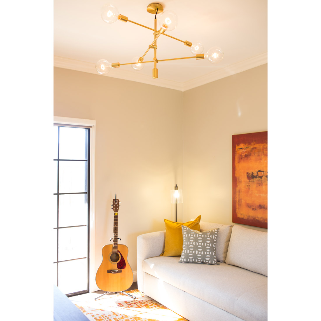 home office music room with sleeper sofa and large artwork and brass globe pendant light yellow, grey and orange accents design by sara bates interior design