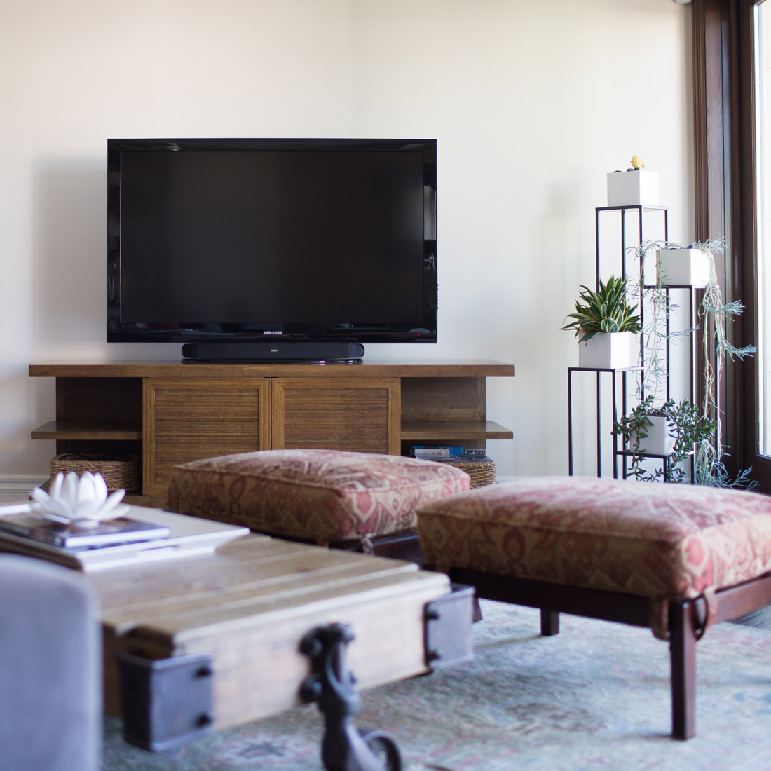 rustic modern living room with bamboo tv console furniture arranged on a diagonal with rustic wood coffee table and upholstered ottomans plant stand with succulents