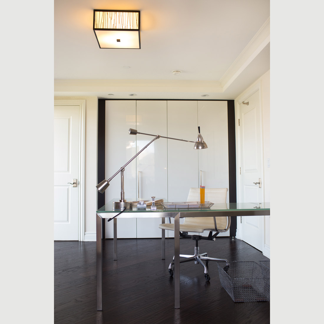modern home office space with dark hardwood floors and white high gloss cabinetry modern glass and metal l shaped desk with counter weight metal task lamp and white leather office chair metal baskets and office accessories