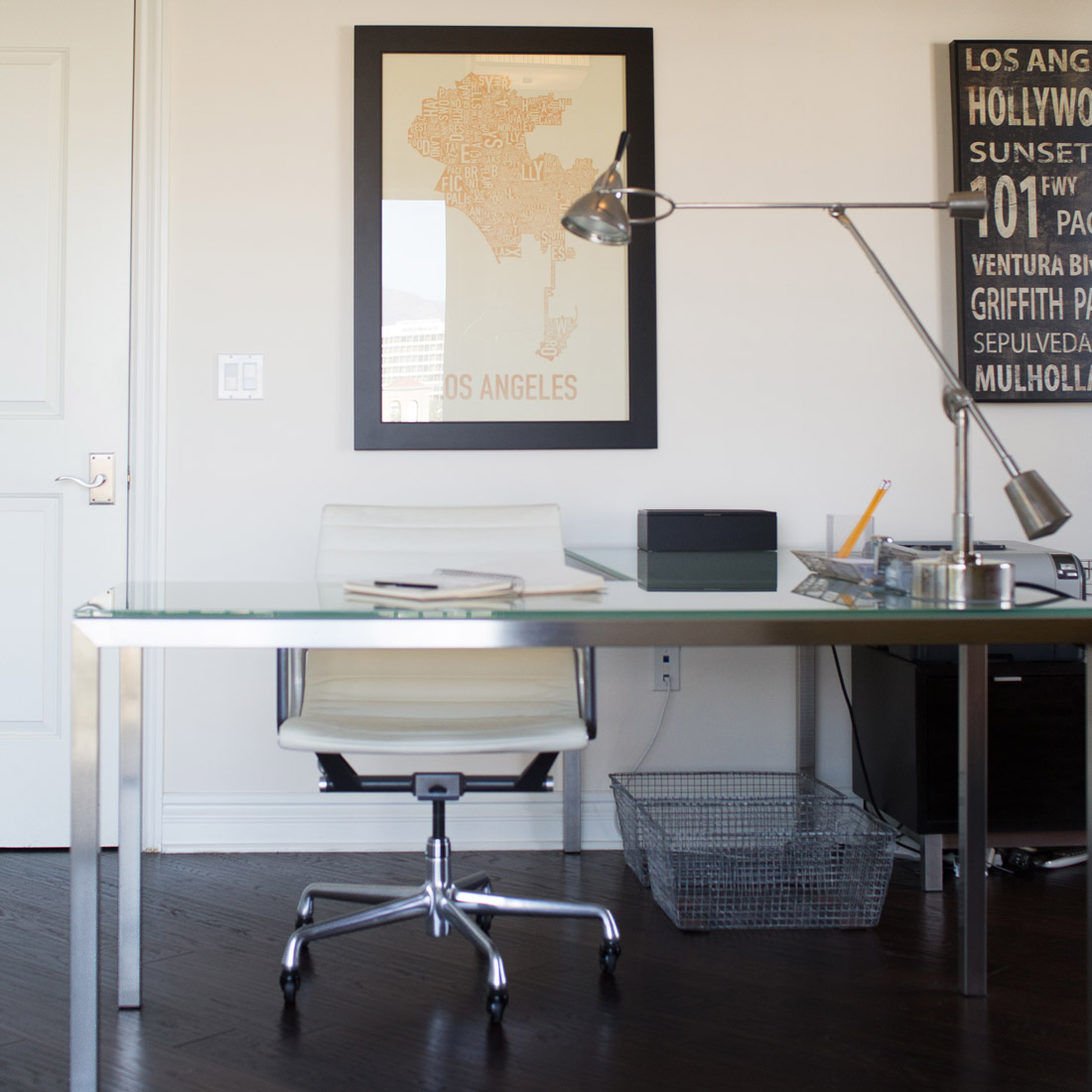 modern home office space with dark hardwood floors and white high gloss cabinetry modern glass and metal l shaped desk with counter weight metal task lamp and white leather office chair metal baskets and office accessories los angles artwork